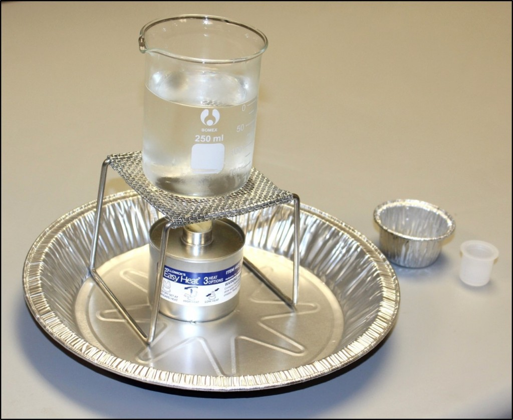 A photo of a fuel canister sitting underneath a burner stand. A 250 mL glass beaker 2/3 full of water is setting on the burner stand. All items are placed in an aluminum pie pan. A 2 oz aluminum cup and the cap for the fuel canister are placed nearby on the countertop.