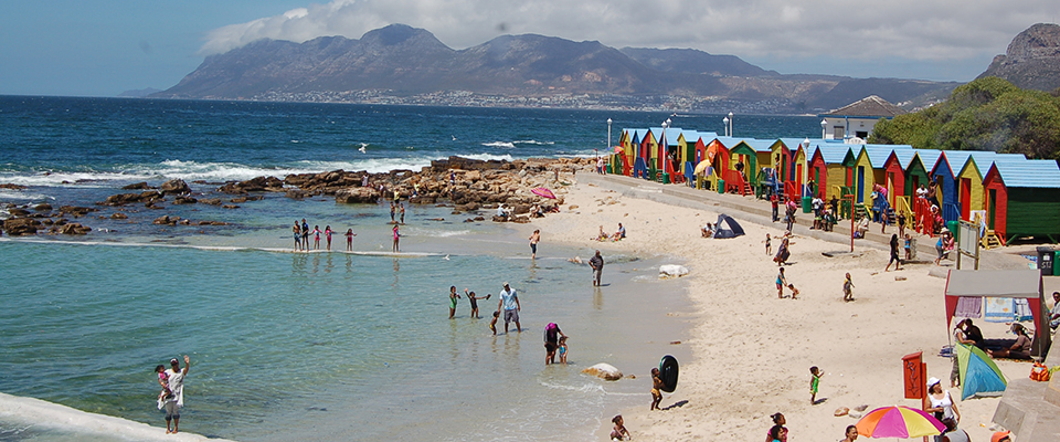 Image of people and colourful huts at St James Beach