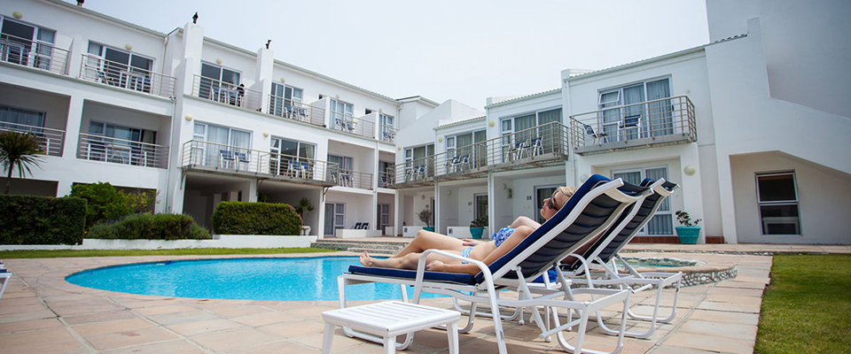 Image of lady lying on lounger by the pool at Arniston Spa Hotel