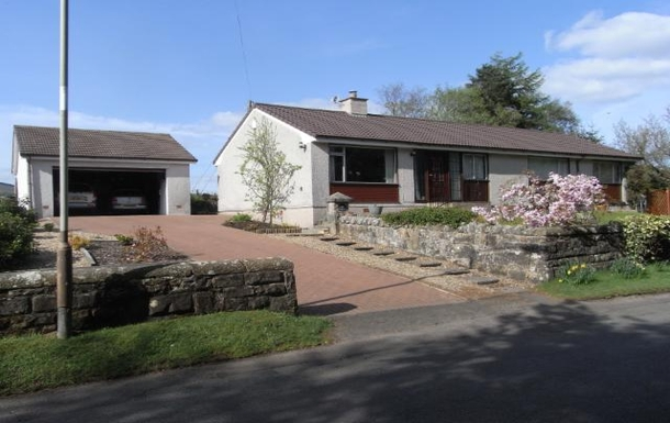 Front of house, large drive and double garage.