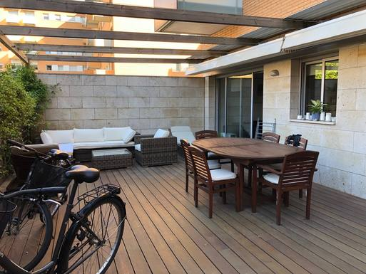 Large terrace with dining area and two bicycles av