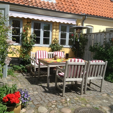 Vores gårdhave med møbler og markise.