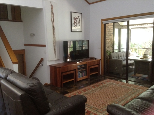 Home exchange in,Australia,WOOLGOOLGA,Living room with screened outdoor room.