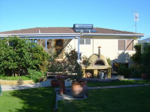 Home exchange in,Australia,ULLADULLA,Back of house with deck and pizza oven