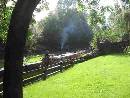 Canal boat passing in lock at bottom of our garden