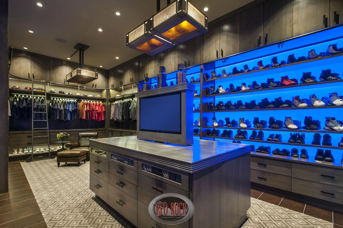 Stunning walk-in closet with custom cabinetry offering plenty of shoe and clothing storage by Red Rock Contractors. There's even a place to relax.