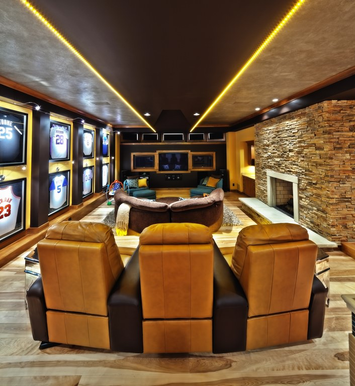 Sports-themed home theater with theater chairs and sofa.