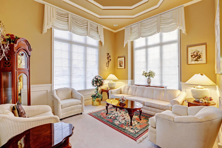 In a traditional, elegant living room, a warm butter yellow on the walls contrasts with the white wainscoting, crown moulding, and furniture. White can seem uninviting sometimes, but a warm color on the walls is a great way to keep the space light and bright. It also draws out the warm undertones of the wooden furniture.