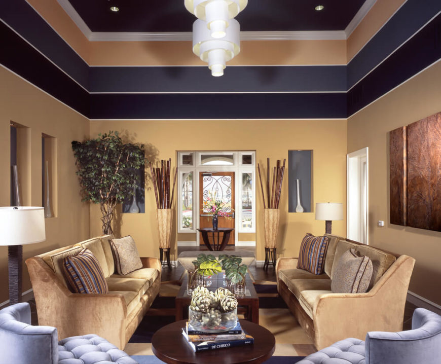 A warm beige on the bottom section of the walls is accented by darker stripes of purple that draw color from the pale lavender chairs on one side of the room. In rooms with tall ceilings, adding treatments to the upper portion of the wall can make a room feel more cozy.