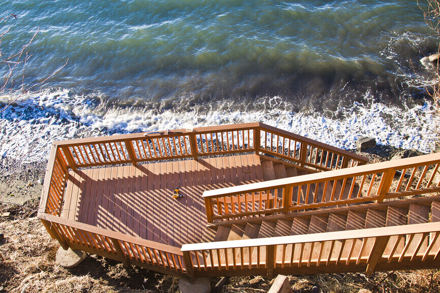 Dramatic deck over rocky ocean with long stairs leading down to it