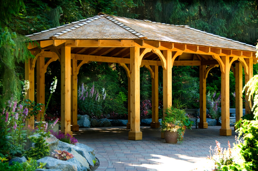 An open design ensures that there's plenty of space for a large gathering to move around without having a traffic jam at the entrance. This gazebo is tucked near a forest and surrounded by flowers.