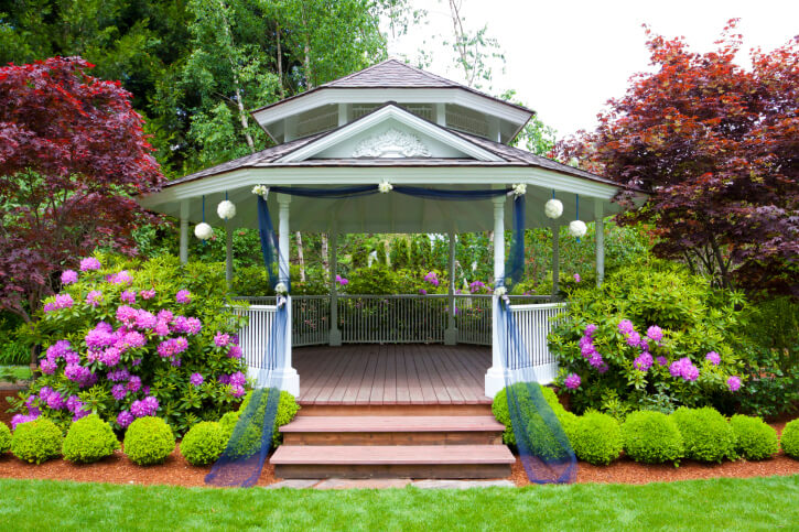 Surrounding your gazebo in large flowering bushes and shrubs creates a secluded retreat. This particular gazebo is enormous and features decorative elements.
