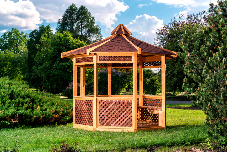 Another Asian inspired gazebo, this time with a unique roof. The differing colors of shingles and supports draw the eye upwards.