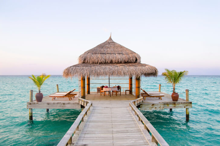This screened gazebo is located at the center of a dock above the turquoise waters of this tropical sea.