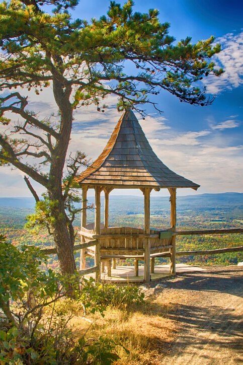 The incredibly tall roof of this small gazebo is shaped somewhat like a witch's hat. It is equipped with rustic benches on four sides.