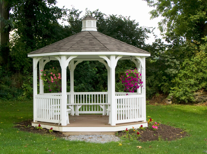 A lovely white gazebo with bench seating all around. This structure is an island in the sea of grass and the foliage behind it allows for some privacy from neighbors.