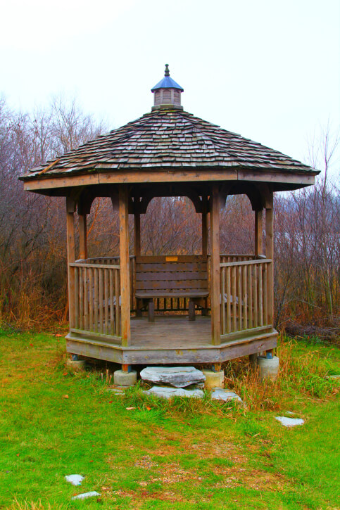 A rustic gazebo in the fall. The structure stands on concrete supports, since the landscape isn't totally flat.