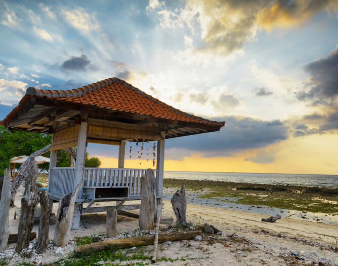 An Asian-inspired gazebo on the beach surrounded by a makeshift driftwood fence. This is a great spot to sit and watch the sunset before leaving the beach for the night.