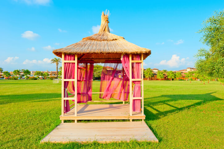 This Soft Top Gazebo Features A Rustic Roof And Magenta Curtains.