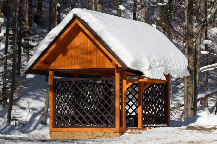 The latticed sides of this gazebo form a kind of screen. The tall gable roof is piled with snow in this stark winter landscape.