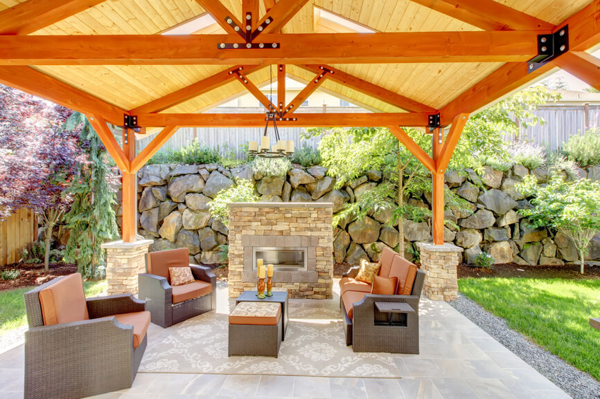 An open rectangular design is perfect for creating a shady patio area. This one has a stone fireplace that matches the stone supports of the structure. The gable roof lets light and air flow in.