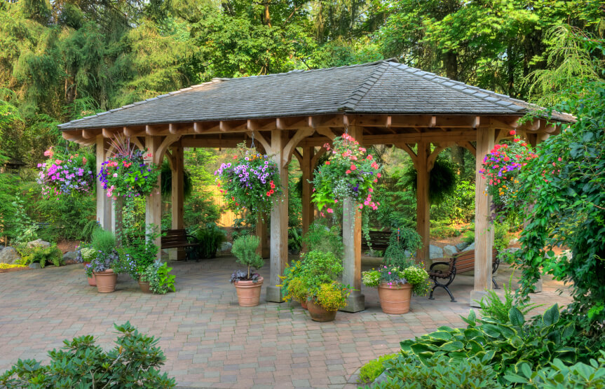 A Garden Pavilion Style Gazebo On Brick Patio While The Surrounding Area Is Lush