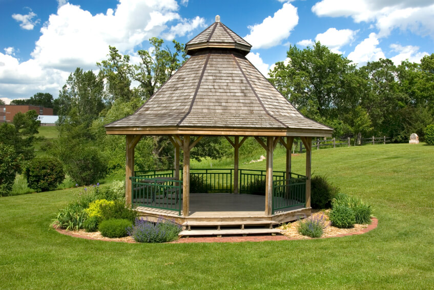 A Large Wooden Gazebo With A Two Tiered Roof, Surrounded By Shrubs And  Bushes.