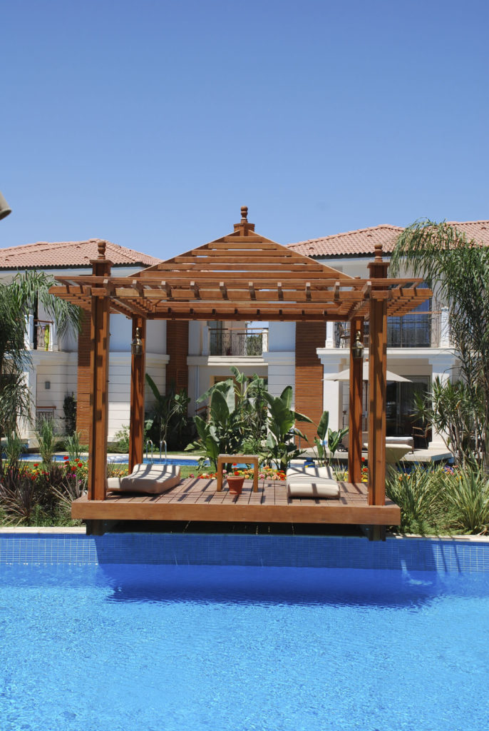 This is a pergola-style gazebo, due to both the open roof and the lattice of bars on the top. The gazebo extends over the side of the pool slightly, making entry easy.