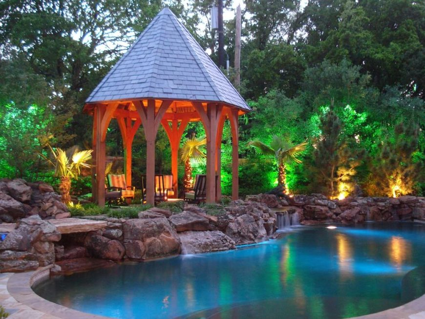 A tall gazebo with a pointed roof, much like a castle turret in fairytales. It sits at the edge of a faux rock waterfall and a pool.