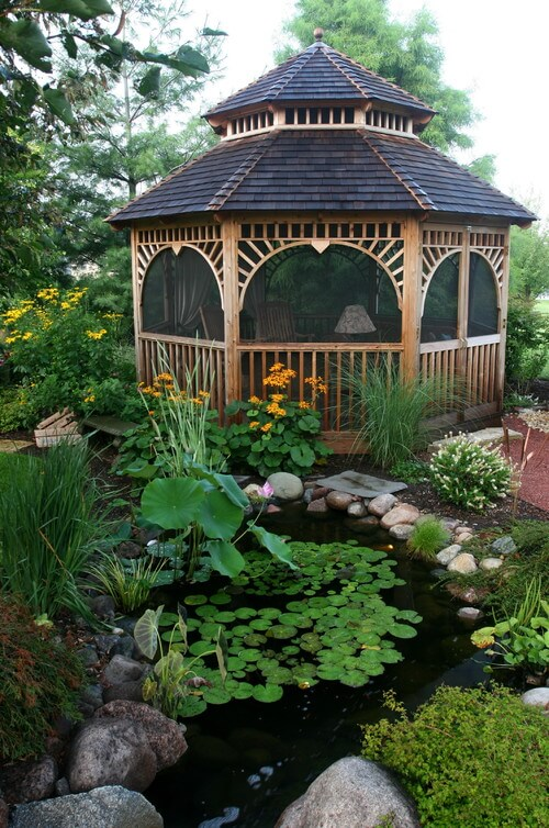 This wooden gazebo has wide edges and sits at the edge of an aqua garden.