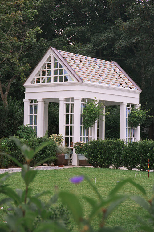 A gorgeous square gazebo with lattice between the pillars. The roof resembles that of a greenhouse.