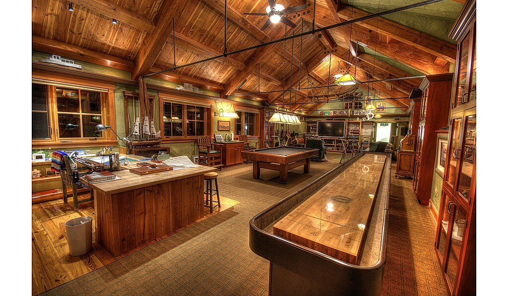 Huge man cave featuring office space, a billiards pool and a living space, all under the stunning vaulted ceiling with exposed beams.