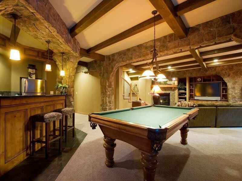 Large man cave featuring a bar area and a billiards pool set on the hardwood flooring, both lighted by pendant lights.