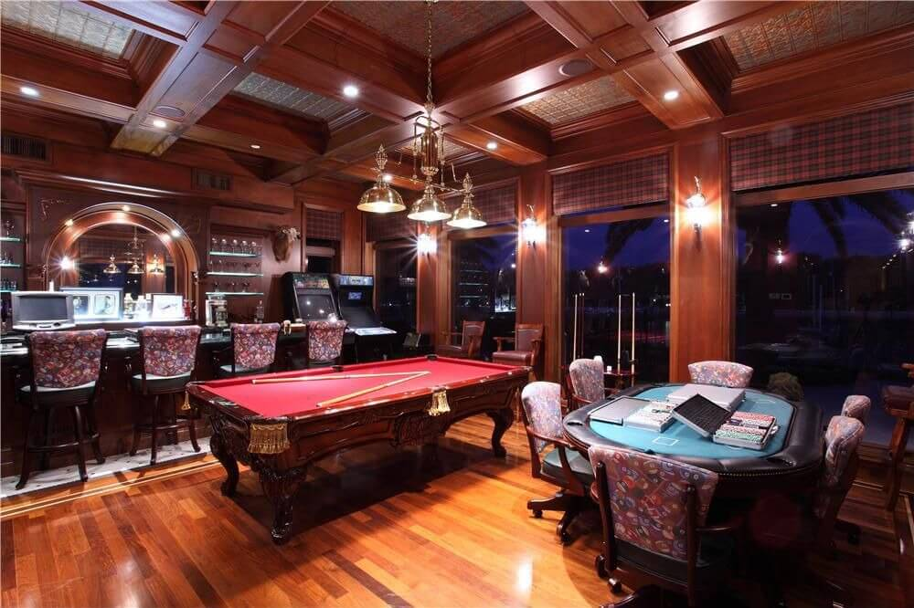 An elegant game room with a billiards pool and a cards table lighted by pendant and wall lights. There's a large bar area.