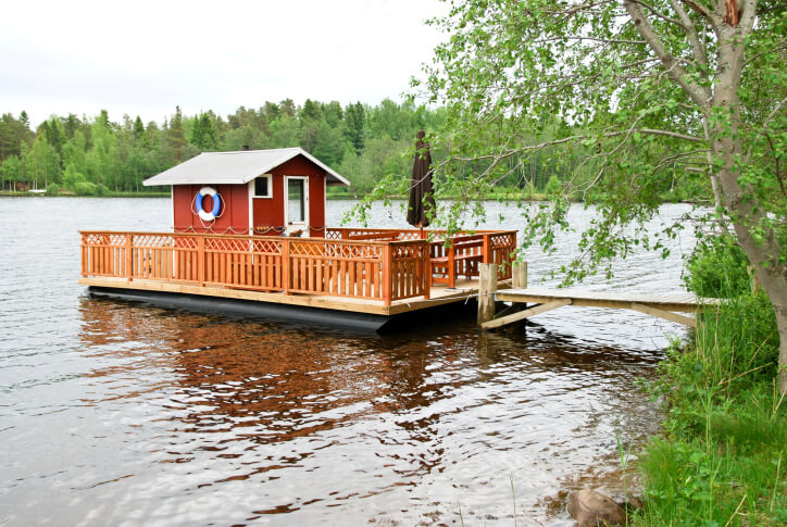 Red sauna hut on dock with deck. A sauna next to a lake is great for cold immersion.