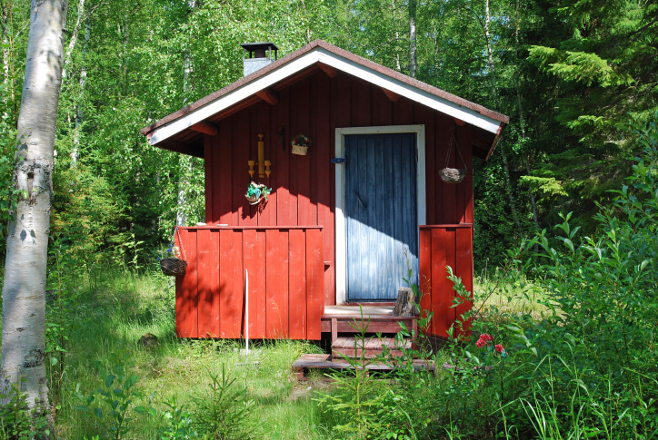 Small traditional red sauna hut with small front deck in the forest.