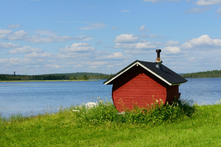 Small red sauna hut built on the edge of a lake