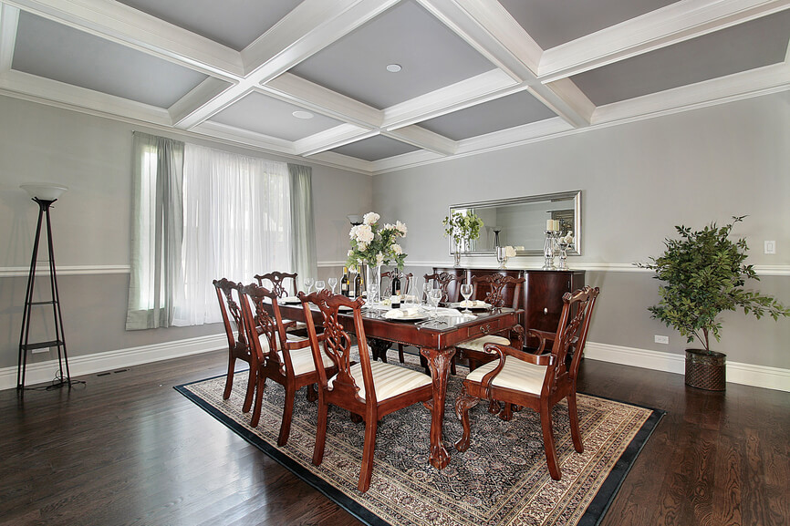 This dining room features a classy dining table set on top of a rug covering the hardwood flooring. The walls look perfect together with the coffered ceiling.