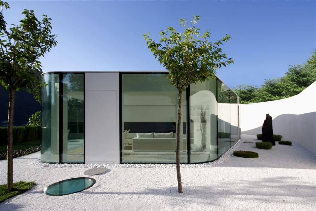 Lake Lugano House is built on a slope which required a retaining wall to create flat surface area for the structure