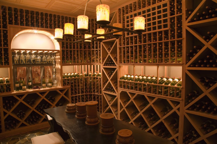 Extensive wine storing capability in this custom wine cellar with long table and benches for an included wine sampling area.