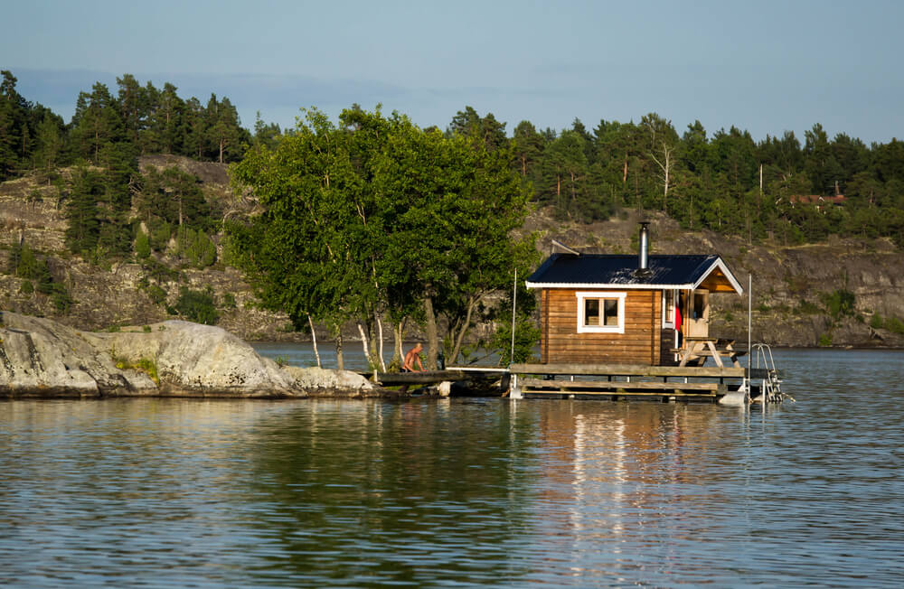 Sauna hut on dock floating on a lake