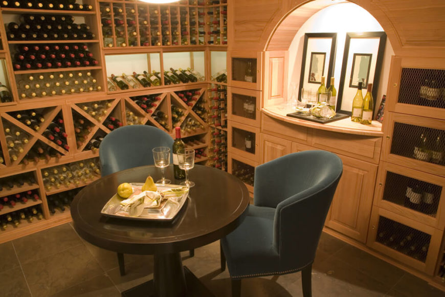 Light wood makes up the custom wine storing cabinets in this wine cellar that includes a wine tasting table for two to four people.