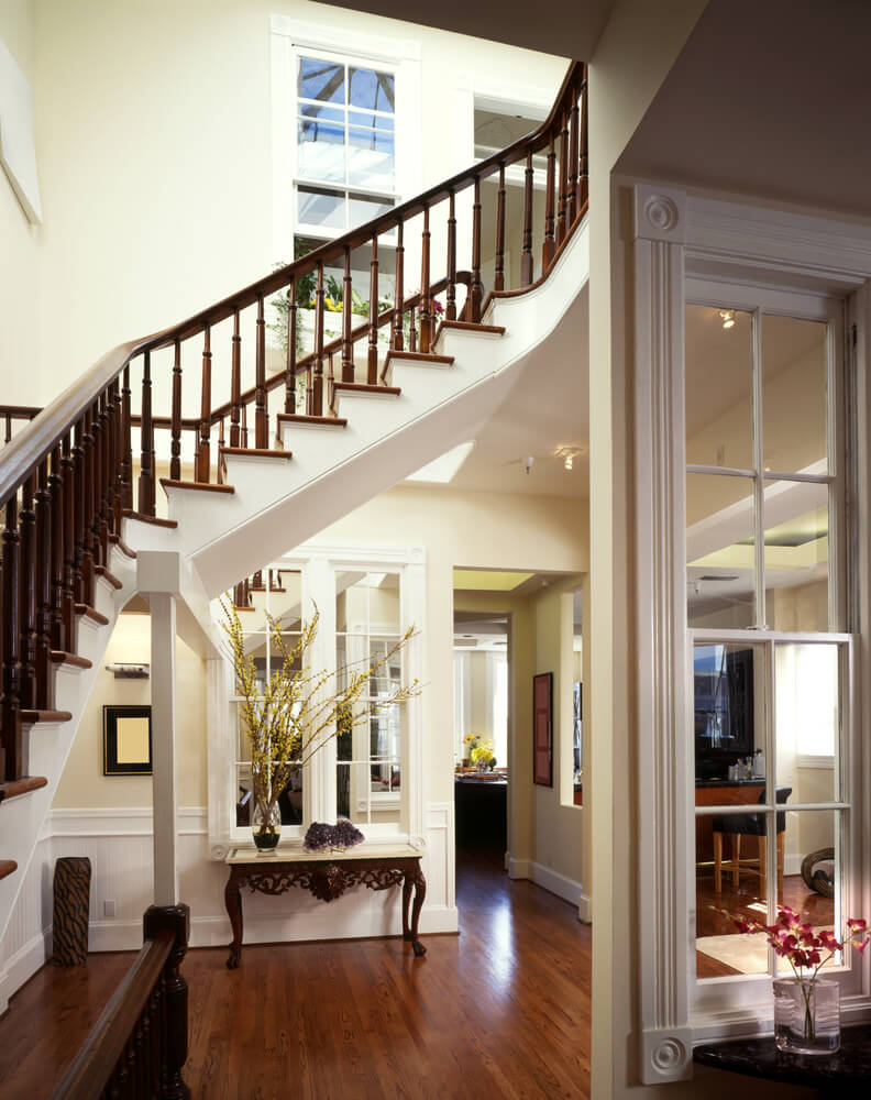 entrance way framed by staircase wrapping around the space - Foyer Design Ideas