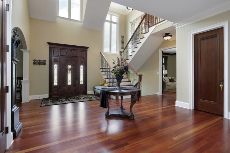 Upscale home with large entry foyer. Half-landing stairs are to the left when facing indoors. Stairs are white and natural wood. Round table is placed in the center of the space. Foyer opens up to other rooms in the home.