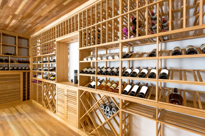 Large diverse set of wine storing cabinets with various wine storing configurations in room with wood floor and ceiling.