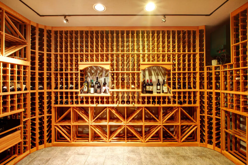 Floor-to-ceiling light wood wine cabinets in dedicated wine cellar room.
