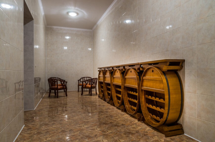 Austere room with custom barrel-style wine storing cabinets and small tasting area at the end of the room.
