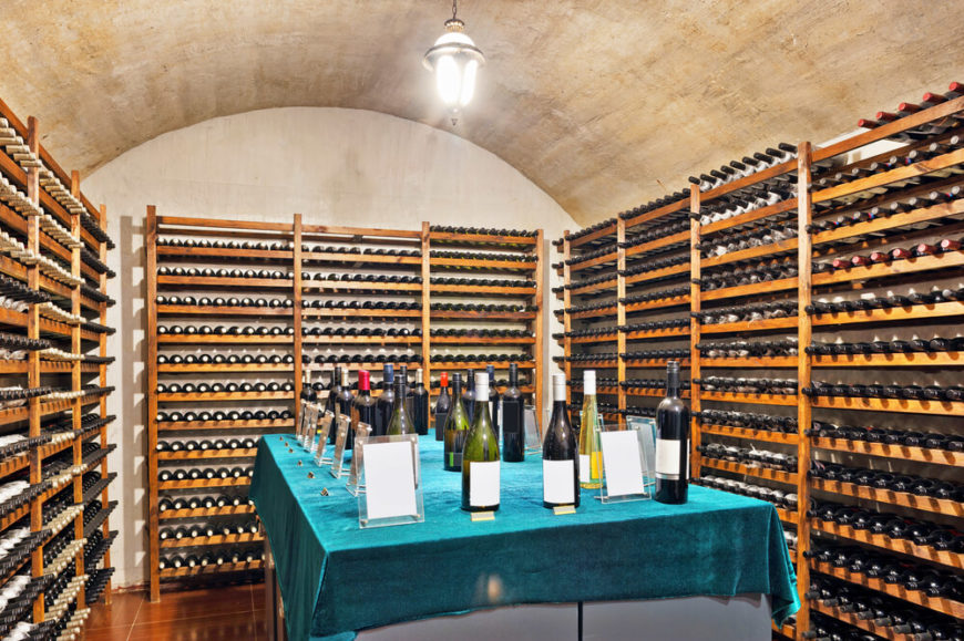 Example of a simple wine cellar with universal wine storing racks throughout and elevated tasting table in the center. This is a simple design that you could implement in any spare part of your basement.