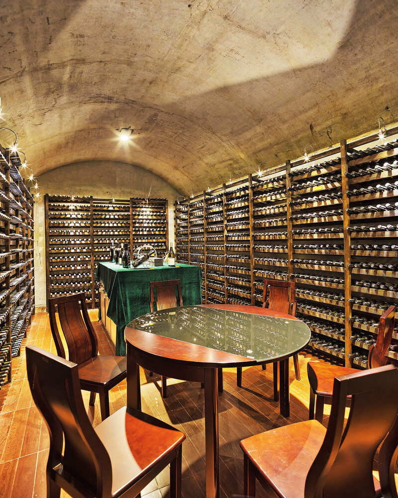 Concrete and wood wine cellar with two tasting areas.