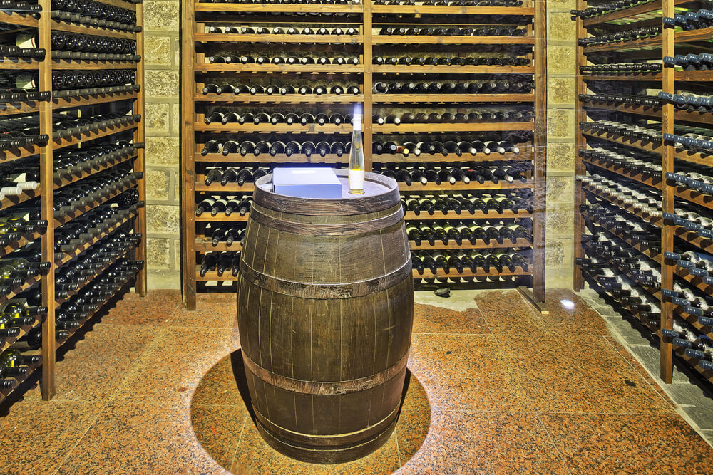 Brick and wood wine cellar with wood barrel in the middle for tasting.
